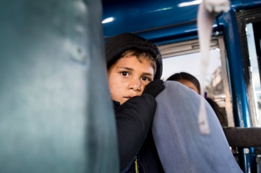 A young boy waits for his bus to leave a migrant shelter hosted at Benito Juarez Sports Complex and head towards El Barretal migrant shelter in Tijuana, Mexico on December 1, 2018. (Zane Meyer-Thornton)