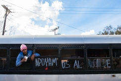 "Jose Miguel waits for a bus to transport him from a migrant shelter located at the Benito Juarez Sports Complex to a new location, El Barretal, a former concert venue. on December 1, 2018 in Tijuana, Mexico. The bus has a sign that reads ""Apoyamos al alcalde"" which means We Support the Mayor. (Zane Meyer-Thornton)"
