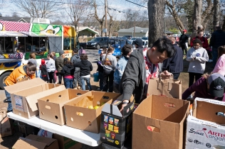 Employees of Trader Joes fill boxes with food for victims of the recent tornado while others line up at Sucker Brunch food truck to receive free lunch.